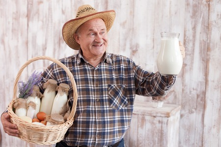 he old: Skillful old farm worker is presenting his work. He is standing and holding a basket and jug of milk. The man is smiling proudly. He is wearing a hat