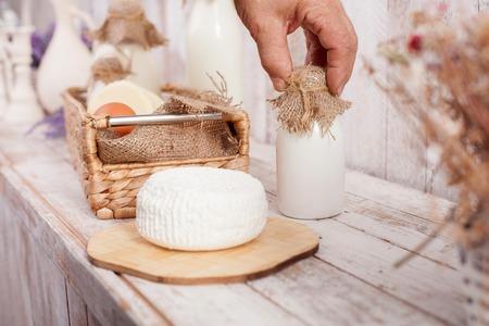 tomando refresco: Cerca de la mano de hombre tocando una botella de leche. Hay una cesta de huevos y queso en la tabla Foto de archivo