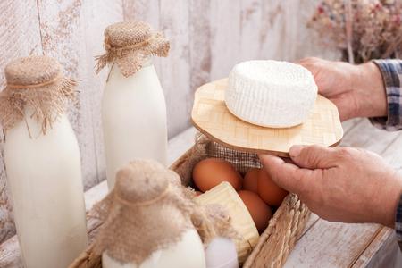 tomando refresco: Cierre para arriba de los brazos del anciano que lleva el queso saludable. Hay una cesta con una botella de leche y huevos sobre la mesa Foto de archivo