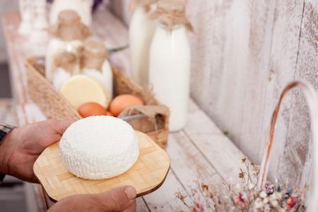tomando refresco: Cerca de las manos de queso viejo hombre que sostiene. El granjero est� de pie cerca de la mesa con una cesta de leche y huevos