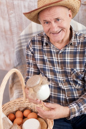 he old: Cheerful old farmer is holding a jar of sour cream. He is sitting in the chair near the basket of dairy products. The worker is looking at camera and smiling