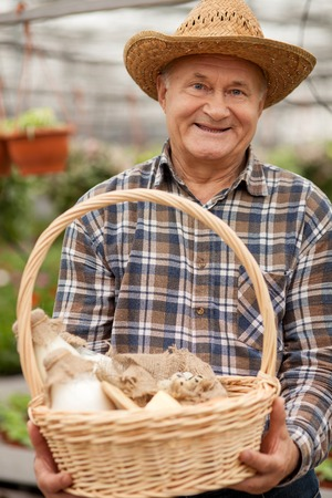 he old: Professional old farmer is presenting a basket of milk and eggs. The man is standing in his garden and smiling. He is looking at camera happily