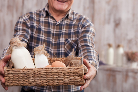 he old: Close up of cheerful old man holding a basket with bottles of milk and eggs. He is standing and smiling