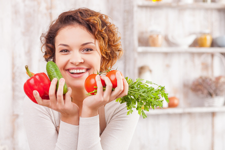 Attractive young woman is holding vegetables in her hands. She is standing in the kitchen and smiling. The lady is looking at camera happily Imagens