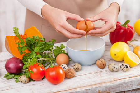 folding arms: Close up of female arms is folding in the bowl an egg. The woman is standing in apron. There a lot of fruits and vegetables on the table