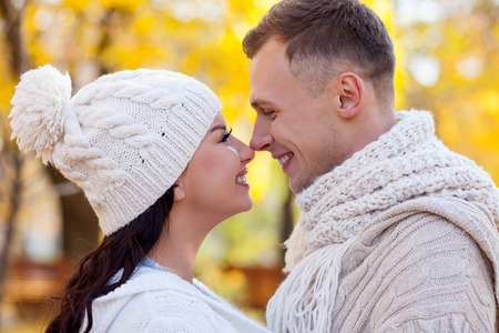 touching noses: Cheerful young loving couple is resting in the autumn park. They are touching noses playfully and smiling. The man and woman are standing and embracing. They are looking at each other with love Stock Photo