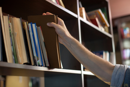 art materials: Close up of male hand of a student taking the book from the shelf in the library Stock Photo