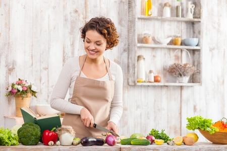Attraente giovane donna è il taglio degli ortaggi in cucina. Lei è in piedi e la lettura di una ricetta dal libro. La signora sta cucinando e sorridente Archivio Fotografico - 48202174