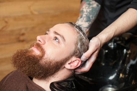 two men: Close up of face of attractive young man with beard at hairdressing saloon. He is getting his hair washed by the barber. The hipster is looking au happily