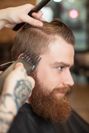 hair clippers: Close up of hands of experienced hairdresser holding clippers and a comb. He is cutting the hair of man carefully. The young bearded hipster is sitting with relaxation