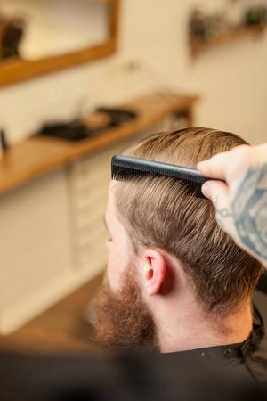 hombres trabajando: Cierre para arriba de los brazos del joven barbero h�bil de peinado al cliente en el sal�n de belleza. El hombre de la barba es que sienta y se relaja