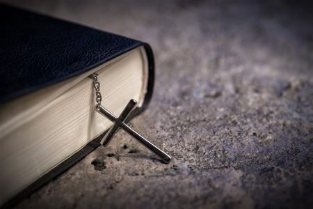 Close up of a Bible with a cross on stone surface Stock Photo