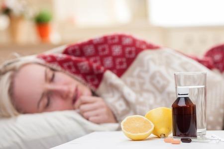 아픈 젊은 여자가 침대에서 자. 그녀는 열이 있습니다. 알약, 레몬, 테이블에 물 한 잔에 초점 스톡 콘텐츠