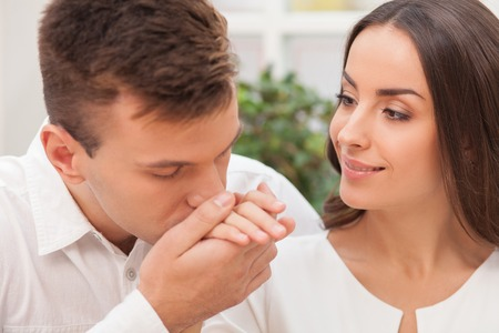gentleness: Cheerful loving couple is dating and flirting. The man is kissing female hand with gentleness. The woman is looking at him with love and smiling