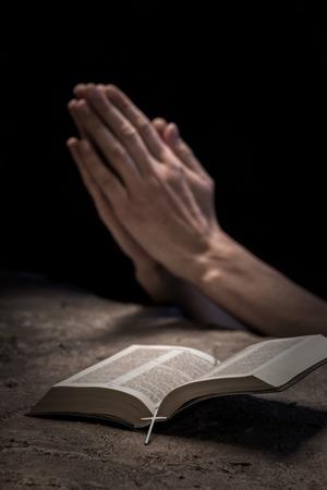 orando: Cerca de las manos de la mujer joven rezando cerca de la Biblia. Ella está aplaudiendo sus brazos juntos Foto de archivo