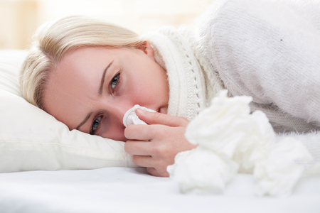 flue: Ill young blond woman is lying in bed with frustration. She has a flue and fever. The lady is blowing into the napkin Stock Photo