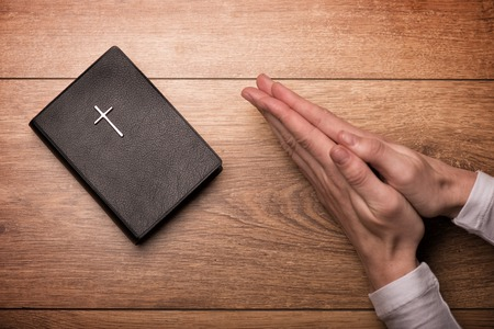 Close up of arms of young woman praying near the Bible. Her hands are clasped on the table