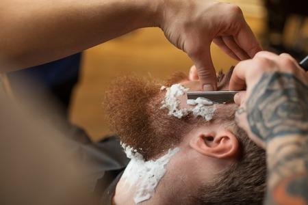 barbero: Cerca de las manos del peluquero de afeitar la barba del cliente. Él está en contacto con una hoja de rostro humano. El hombre está sentado en la silla con la concentración