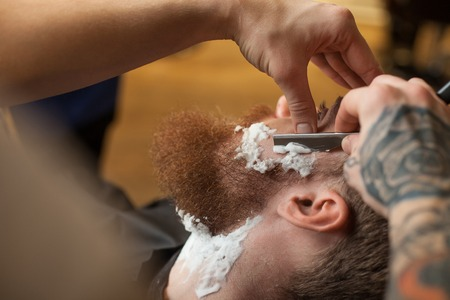 barber shop: Close up of hands of barber shaving beard of the customer. He is touching a blade to human face. The man is sitting in chair with concentration