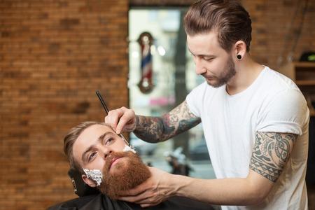 cuchillo: Peluquero atractivo es el afeitado la barba masculina con el cuchillo. Él está de pie y mirando a la cara humana de alegría. El hombre de la barba se está sentando con seusness Foto de archivo