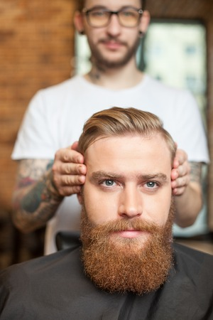 hygeine: Cheerful young hairdresser is making decision about the hairstyle of the customer. He is standing and touching the hair of guy. The bearded man is sitting and serious face Stock Photo