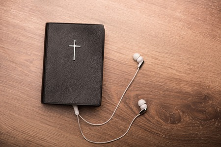audio book: Close up of a Bible connected with earphones Stock Photo