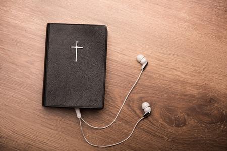 Close-up van een bijbel in verband met oortelefoons Stockfoto