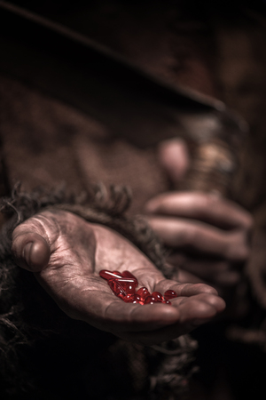 narcotism: Close up of hands of grim Reaper holding red narcotic pills and scythe Stock Photo