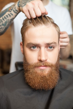 hygeine: Close up of hands of barber making a hairstyle for man. He is standing and touching male hair. The young hipster with a beard is looking forward with seriousness