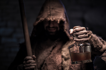 Grim Reaper is holding a bottle of alcohol drink. The man is standing and smiling. He is carrying a scythe and laughing