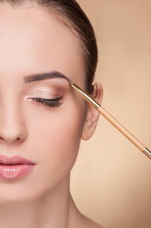女性の顔の半分のクローズ アップ。美しい女性はアーティストを確認を得ています。美容師は、彼女の眉にブラシを触れています。女の子が冷静さ