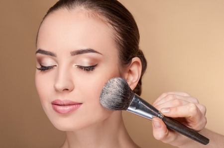makeup fashion: Close up of hand of professional make-up artist applying powder on female check. She is holding a brush. The woman closed eyes with pretty smile Stock Photo