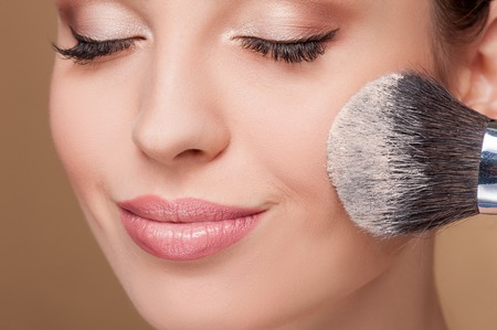 makeup fashion: Close up of face of young woman getting powder on her cheek with a brush. She is smiling. Her eyes are closed Stock Photo