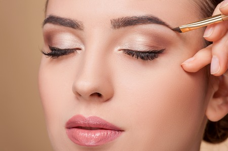 up: Close up of beautiful face of young woman getting make-up. The artist is applying eyeshadow on her eyebrow with brush. The lady closed eyes with relaxation Stock Photo