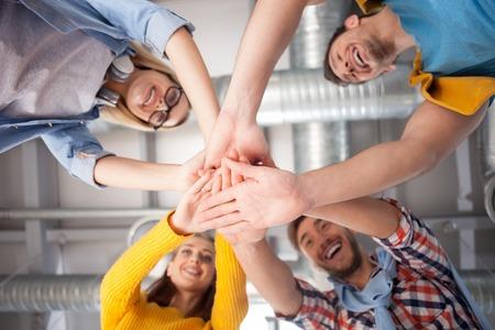 明るく創造的なチームは喜びで手に参加します。彼らは喜びとの連携に取り組んでいます。男性と女性が立っていると笑みを浮かべて 写真素材