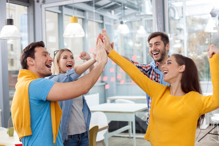 Skillful young colleagues are celebrating their success. They are raising hands and giving high-five. The men are woman are smiling Stock Photo