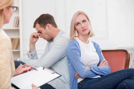 insult: Young married couple has problems in their relationship. They are sitting in office of psychologist with insult. The woman is listening to them and making notes