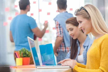 陽気な若い創造的なチームは、新しいプロジェクトを議論しています。女性は、机に座って、ノート パソコンを使用します。彼らは笑っています。