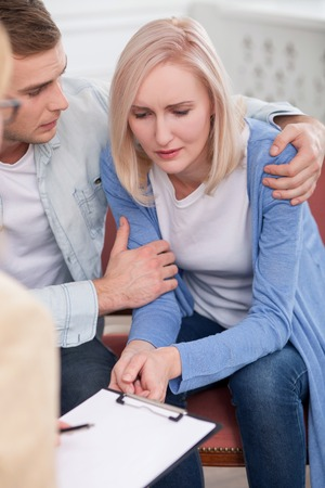 Pretty young husband and wife are asking advice in psychologist. The blond woman is crying with depression. The man is embracing her with love. The lady is sitting and making notes