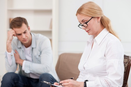 seriousness: Experienced psychologist is consulting young man. She is sitting on sofa and writing with seriousness. The man is crying and looking down with depression