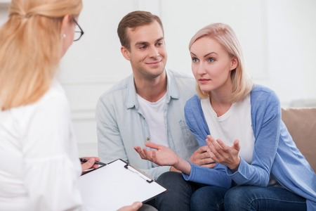 wife and husband: Attractive husband and wife are visiting a psychologist. The woman is trying to explain something to therapist with aspiration. The man is looking at her with love and smiling