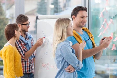 experienced: Experienced young designers are discussing new project. They are standing near the whiteboard and smiling. The man is drawing on a blueprint. The woman is looking at it with interest Stock Photo