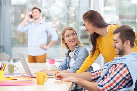 smiling businessman: Experienced creative team is working together in office. They are sitting at the desk and smiling. The woman is using a laptop. The man is standing and talking on mobile phone on background Stock Photo