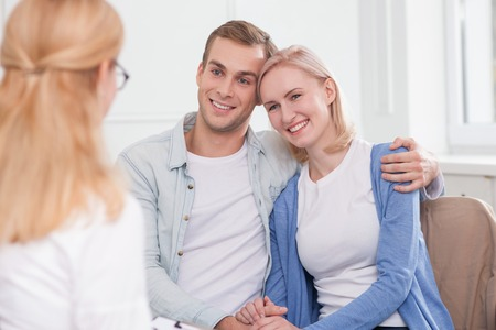 doctor woman: Beautiful young husband and wife are visiting a psychologist. They are sitting and embracing. The family is smiling with happiness