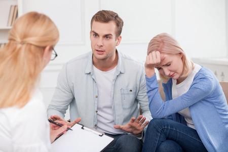 casados: Alegre joven matrimonio tiene problemas con sus relaciones. Están sentados y consultar con un psicólogo. La mujer está llorando de desesperación. El hombre es molesto