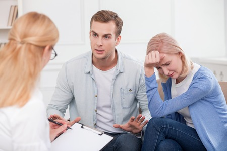 married: Cheerful young married couple has problems with their relationships. They are sitting and consulting with a psychologist. The woman is crying with desperation. The man is upset Stock Photo
