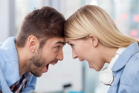 happiness or success: Skillful young colleagues are congratulating each other with success. They are standing and touching foreheads. The man and woman are screaming with happiness and smiling Stock Photo