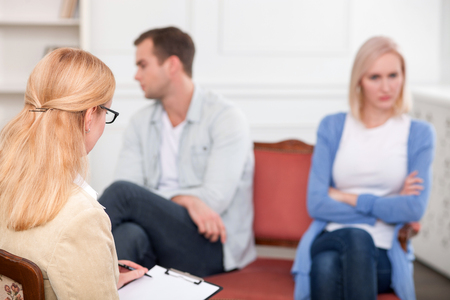 insult: Experienced psychologist is consulting young married couple. She is listening to them attentively and writing. The husband and wife are sitting far from each other with insult