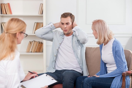husband: Young married couple has problems and using marriage therapy. The wife is trying to explain her feelings to her husband with insult. He do not want to listen her and covering ears with hands Stock Photo