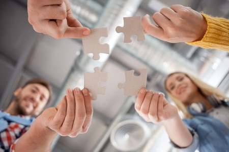 Close up of hands of creative team joining pieces of puzzle together. The men and women are standing and smiling Stockfoto